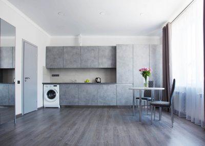 Kitchen, table, chairs, window, washing machine. Suite room in Sumskaya Apartments, Kiev, Ukraine.